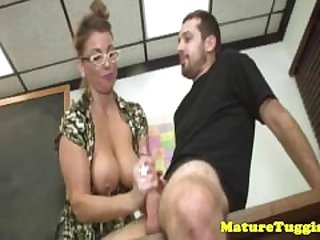 Mature tugging teacher makes student cum